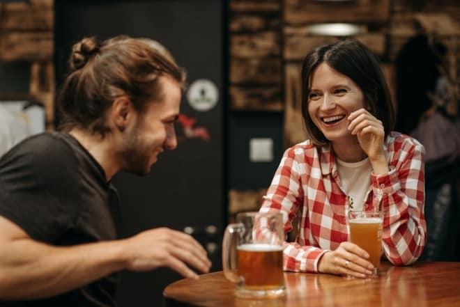 Dos personas bebiendo y riendo juntos - preguntas personales para conocer a alguien