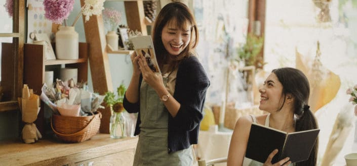 Dos chicas divirtiéndose en una tienda de flores