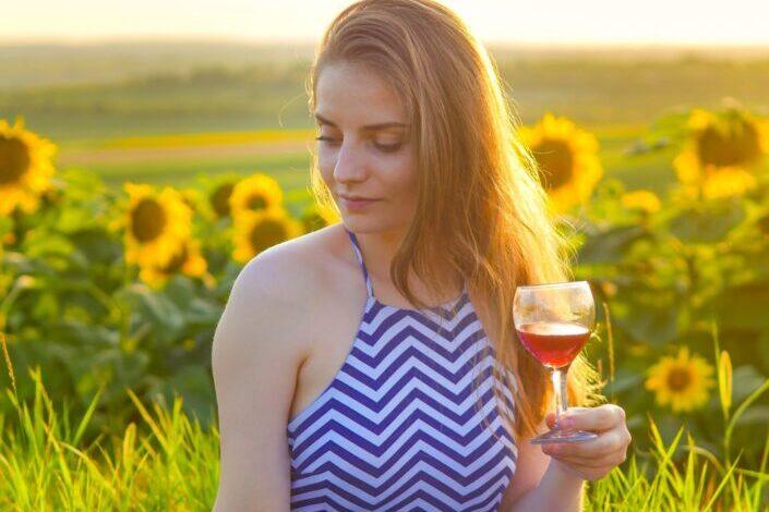 Bella mujer sosteniendo una copa de vino en medio del jardín de girasoles