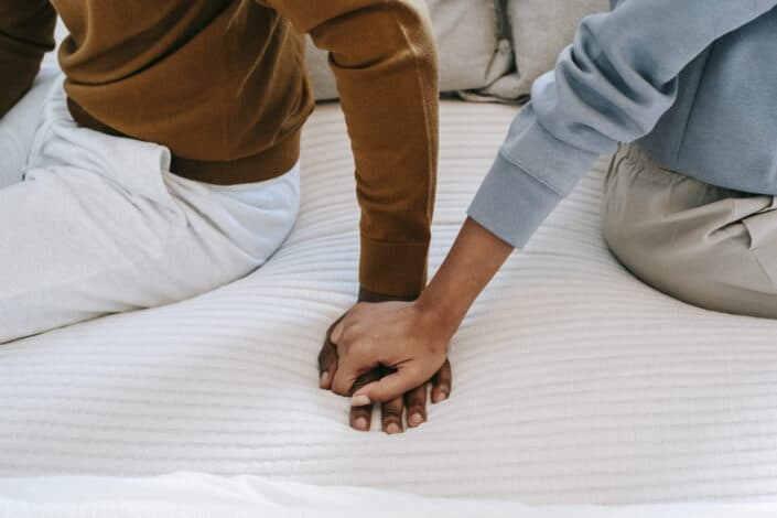 mujer tocando la mano de su hombre en la cama