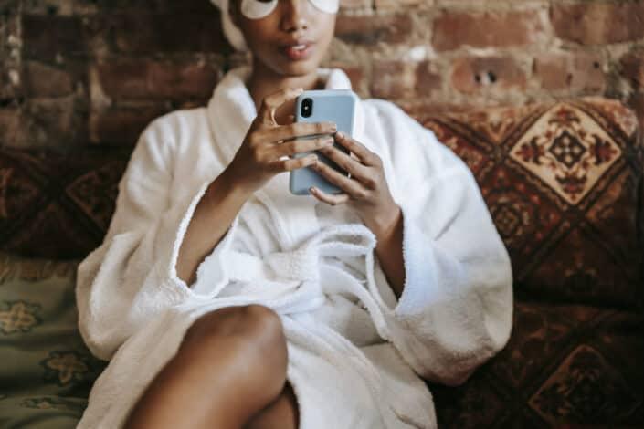 Señora en su bata de baño y antifaz sentada en un sofá ocupada en su teléfono