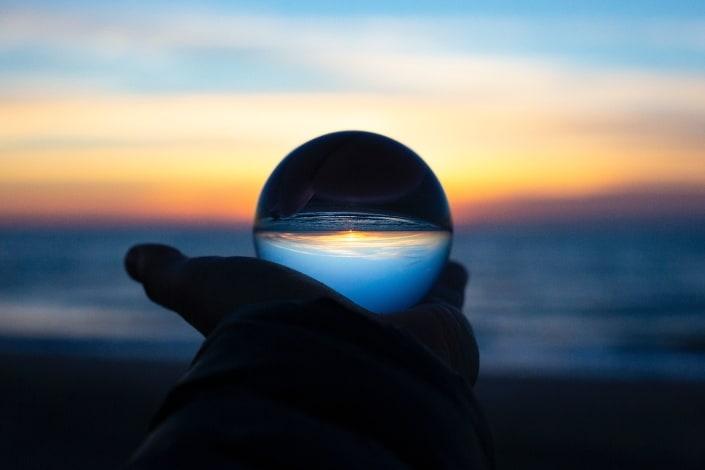 Esfera que refleja la puesta de sol en una playa