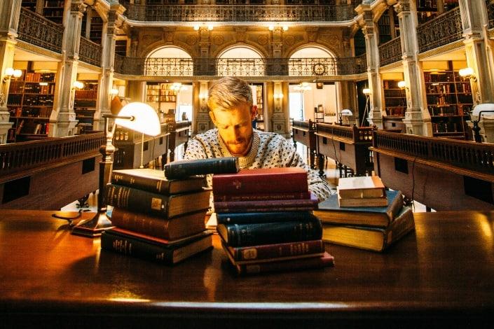 hombre en una biblioteca con libros frente a él