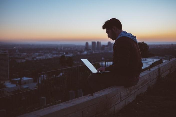 hombre sentado en la repisa con laptop