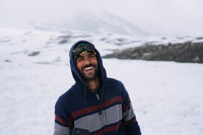 Guy riendo mientras está de pie sobre la nieve