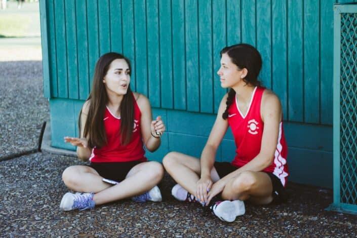 Dos mujeres vestidas con uniforme deportivo sentados en el suelo y hablando