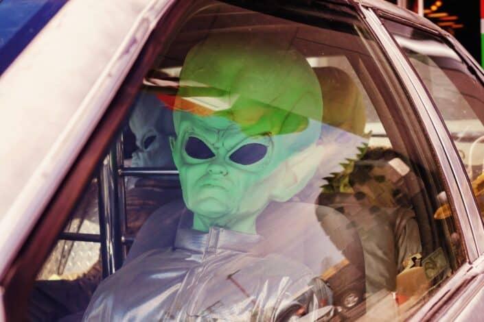 Grupo de amigos vistiendo traje alienígena sentado en un coche