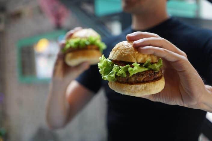 Chico sosteniendo una hamburguesa en cada mano