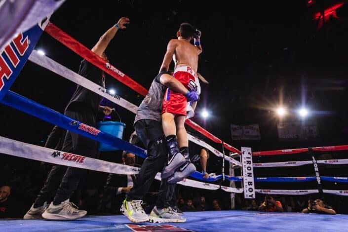 Boxeador siendo izado después de ganar