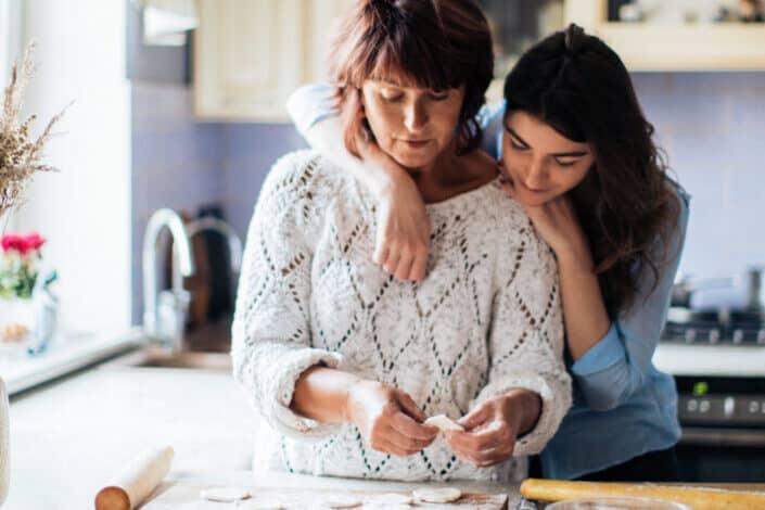 Mujer inclinada sobre su mamá mientras mira un trozo de papel