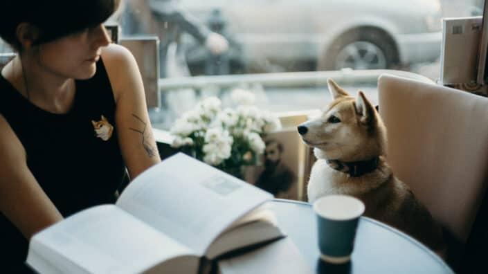 Mujer sentada en el café con su perro a su lado