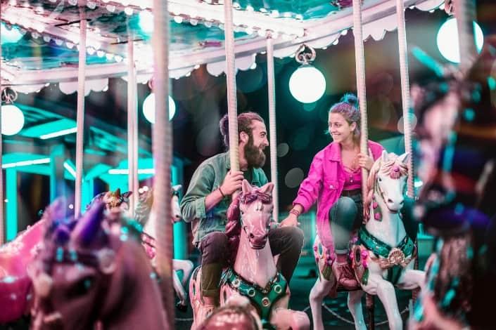 pareja montando un carrusel en una cita romántica