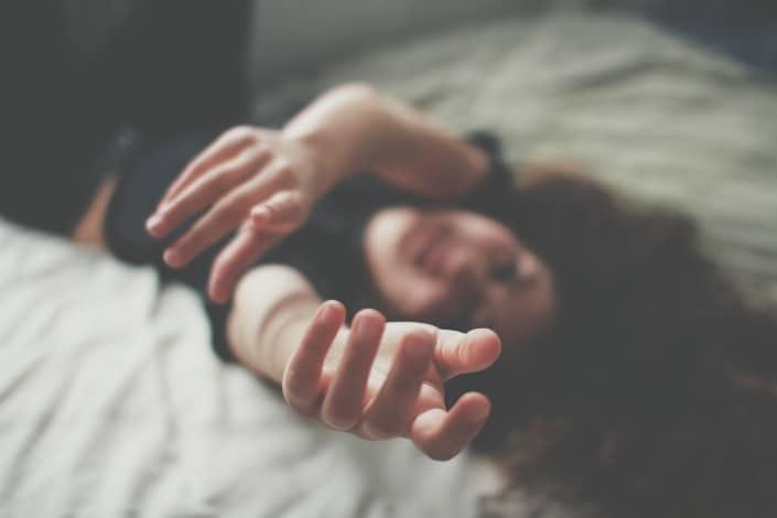 una foto borrosa de una mujer acostada extendiendo sus manos