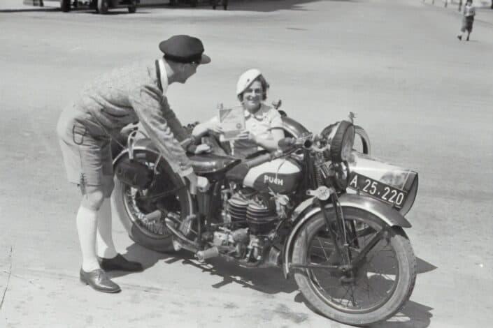 Foto de época de un hombre y una mujer montando una vieja moto