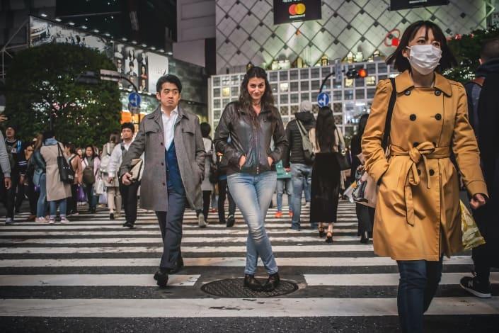 Señora vistiendo una chaqueta de cuero tomando pose en un concurrido paso de peatones