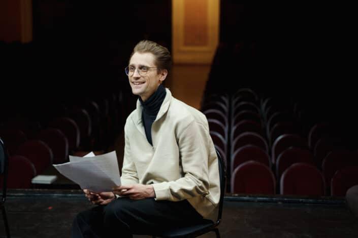 Hombre con gafas sosteniendo su guión para un espectáculo de teatro