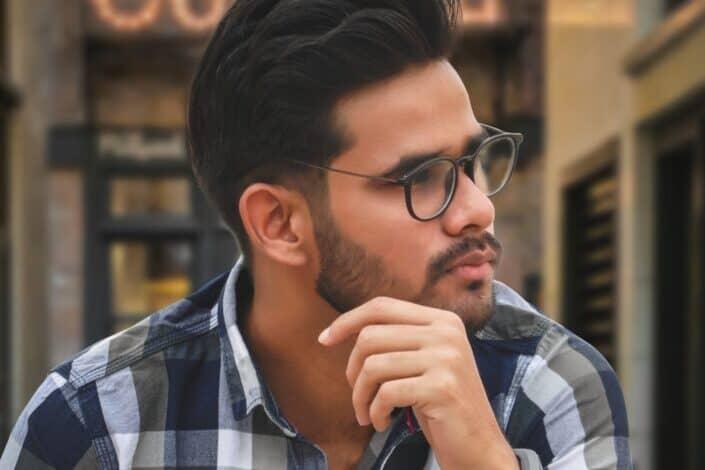 Hombre con gafas vistiendo una camisa a cuadros en pensamiento profundo