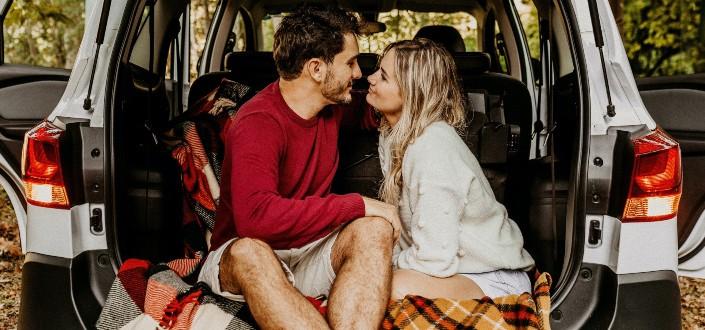 pareja sentada en la camioneta de su coche teniendo momentos dulces