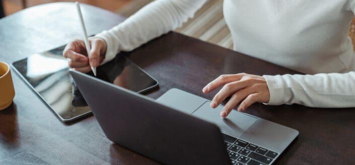 emprendedora haciendo trabajo multitarea en diferentes dispositivos