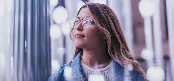 dama con gafas mirando fuera del cristal de la ventana