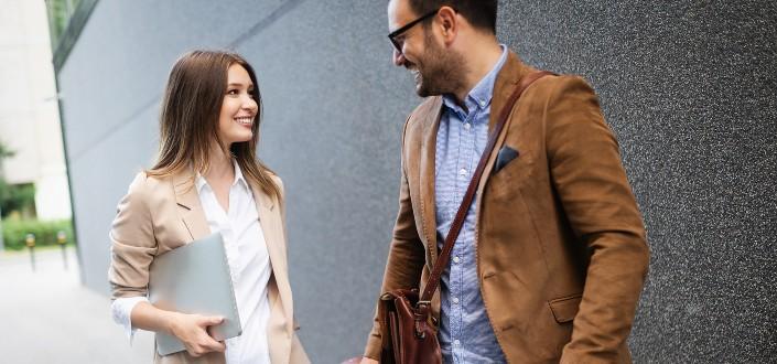 Dos pareja corporativa mirando el uno al otro y sonriendo