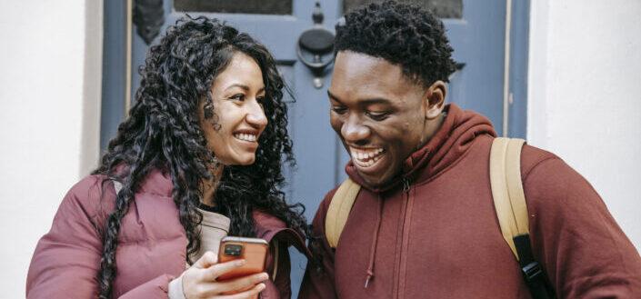 Alegre pareja multirracial compartiendo smartphone en las calles de la ciudad