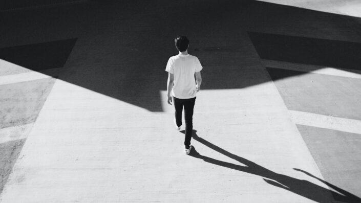 Hombre caminando por la carretera de hormigón gris