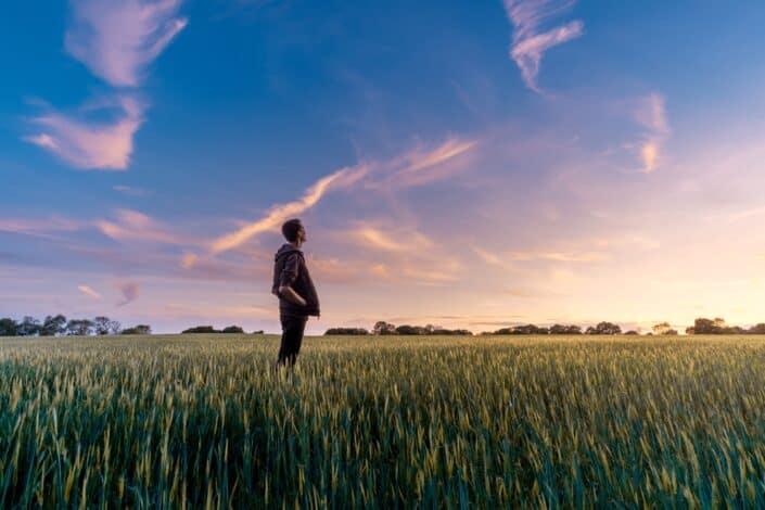 hombre en el campo de hierba mirando al cielo
