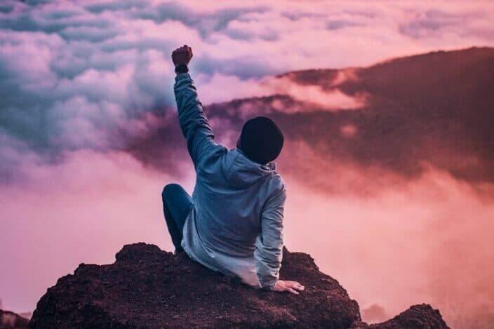 Hombre sentado en el borde de una montaña con vistas al mar de nubes