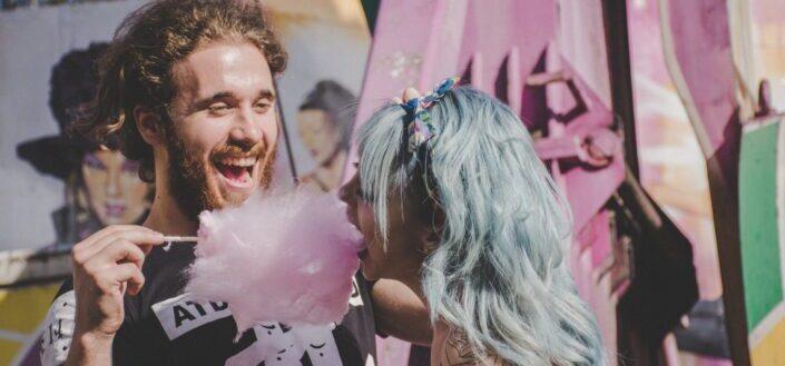 pareja comiendo algodón de azúcar en un festival