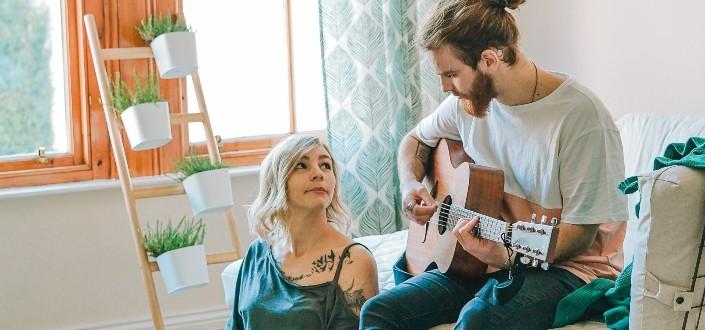 señora escuchando a su hombre tocando la guitarra