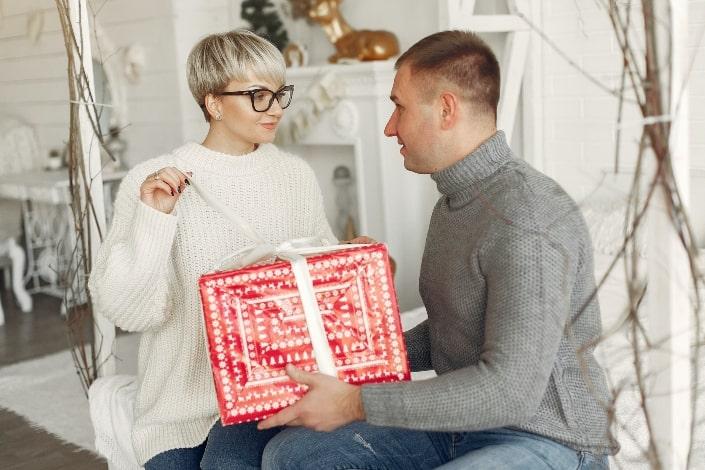 mujer abriendo su regalo de su hombre
