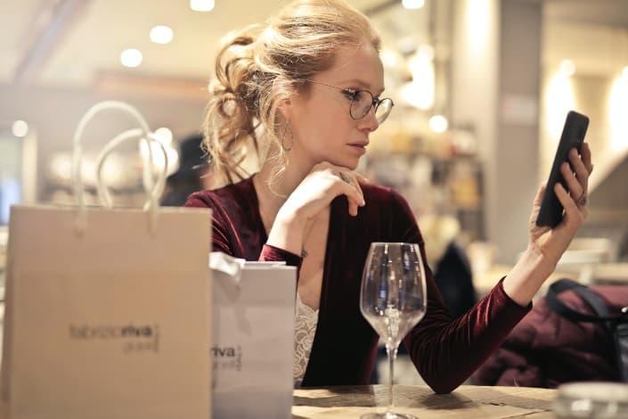 mujer con anteojos terminó con su vino mirando su teléfono