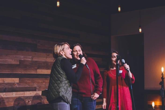 Amigas disfrutando de una actuación de karaoke