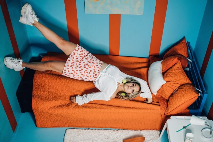 Mujer con camisa blanca acostada en el sofá naranja