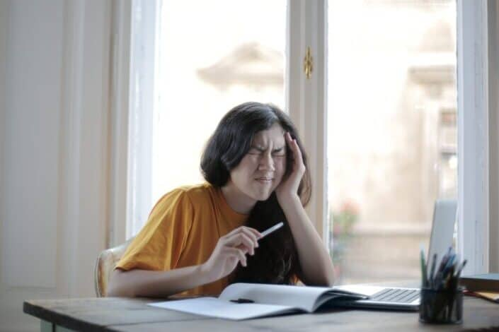 estudiante que sufre dolor de cabeza en casa