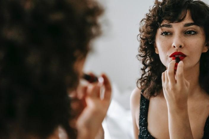 mujer encantadora aplicando lápiz labial rojo