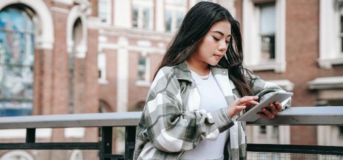 Mujer asiática charlando en el teléfono inteligente en el puente de la ciudad