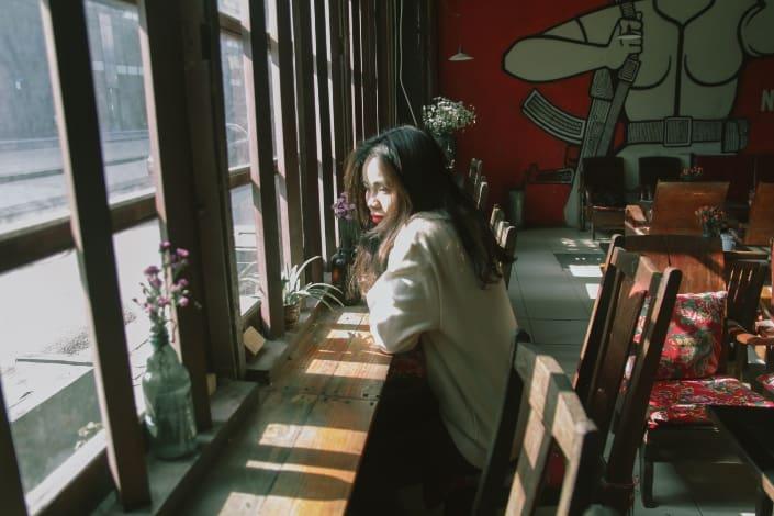 mujer sentada en una silla cerca de la ventana
