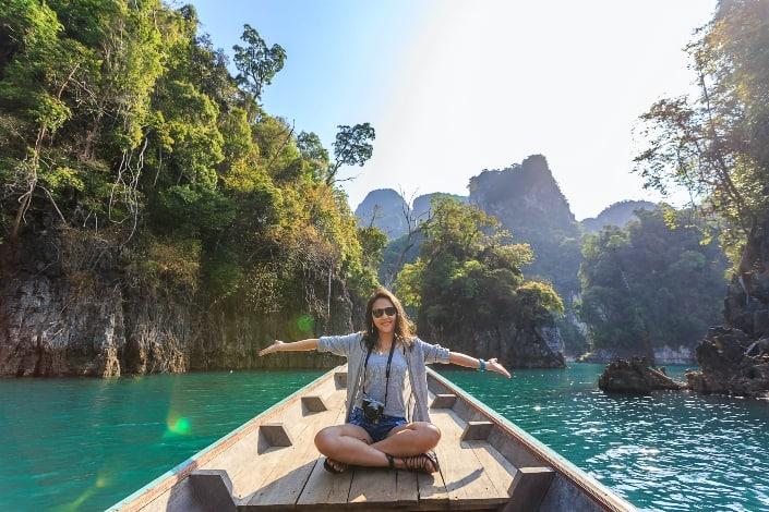 mujer sentada en el barco extendiendo sus brazos