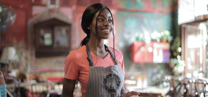 sonriente mujer de servicio en su delantal