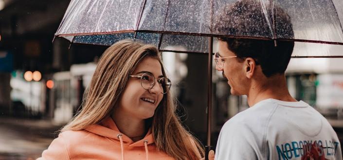 pareja que tiene conversaciones dulces bajo un paraguas mojado