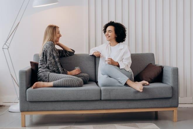 Mejores amigos teniendo tiempo de calidad en el sofá - preguntas personales para hacerle a una chica