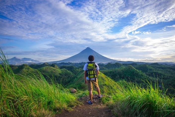 excursionista disfrutando de una hermosa vista de una montaña de cono perfecto