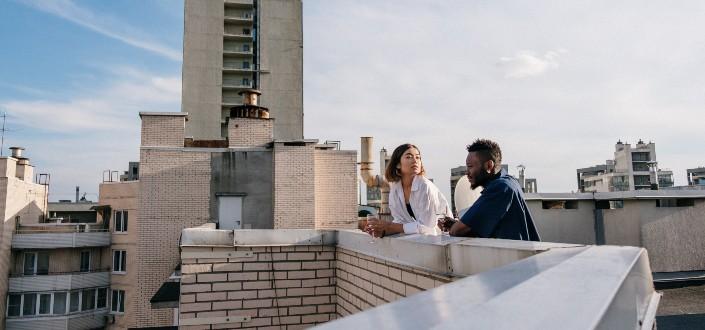 hombre y mujer hablando en una azotea en un clima agradable