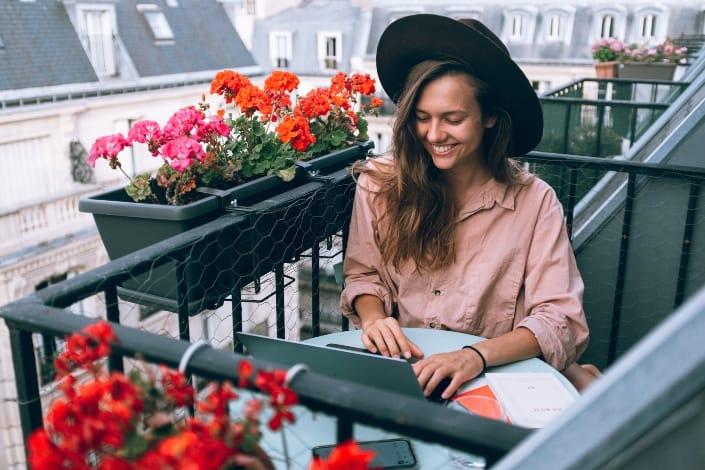 Woman wearing beige dress using laptop computer