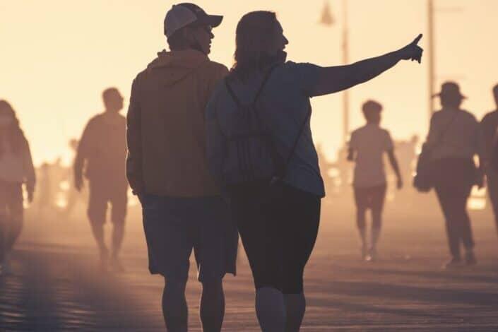 silueta, de, hombre y mujer, ambulante, en, arena