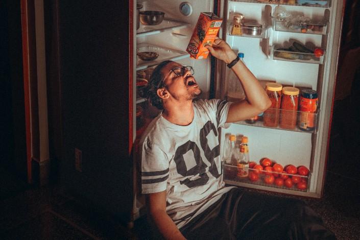 hombre bebiendo detrás de una nevera abierta