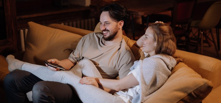 happy couple sitting on the couch while watching movie