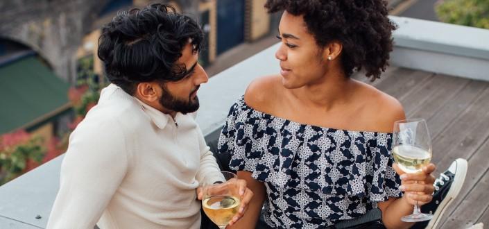 pareja romántica disfrutando del vino en una azotea